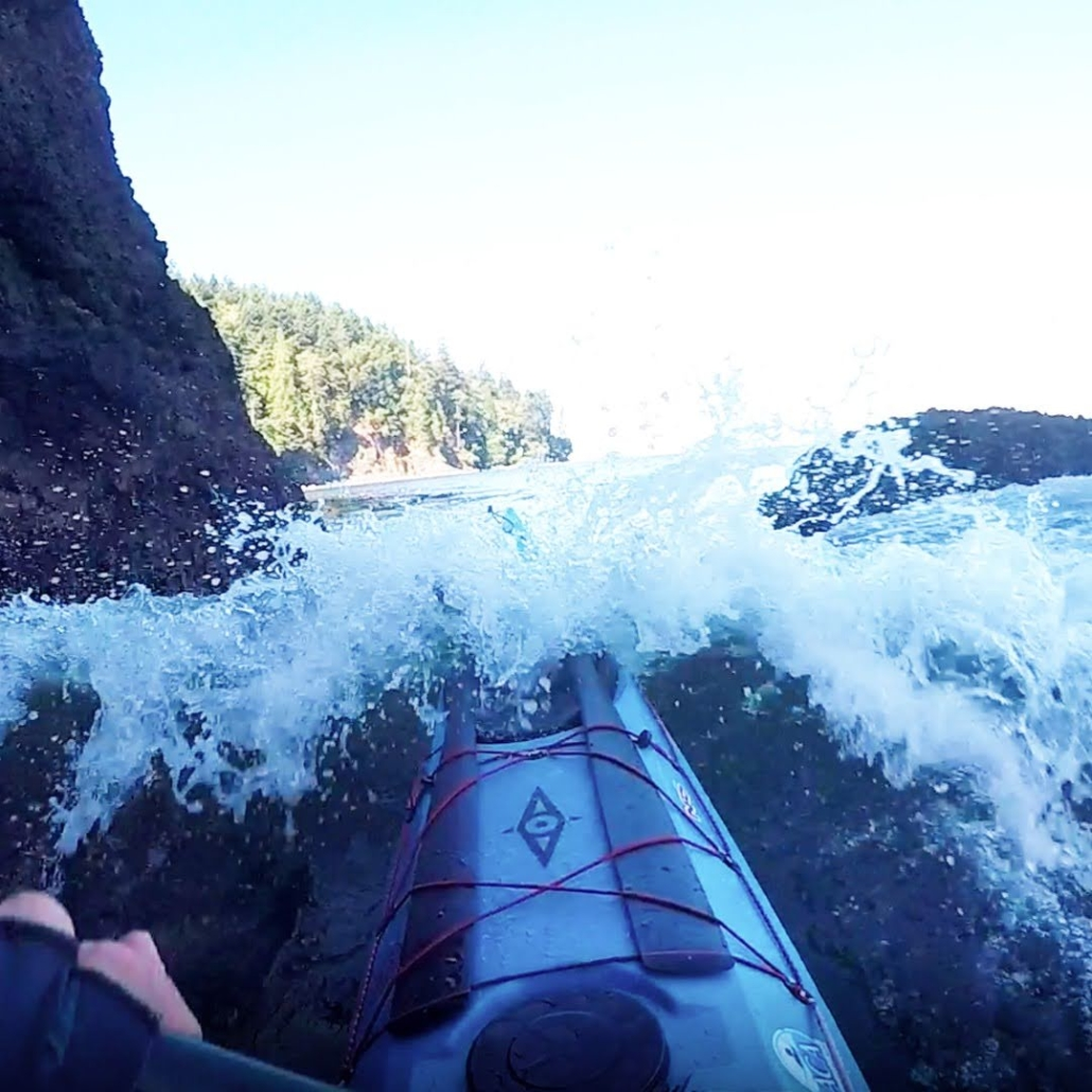 Water breaking over the bow of the Whisky 16 sea kayak while rock gardening in the Strait of Juan de Fuca
