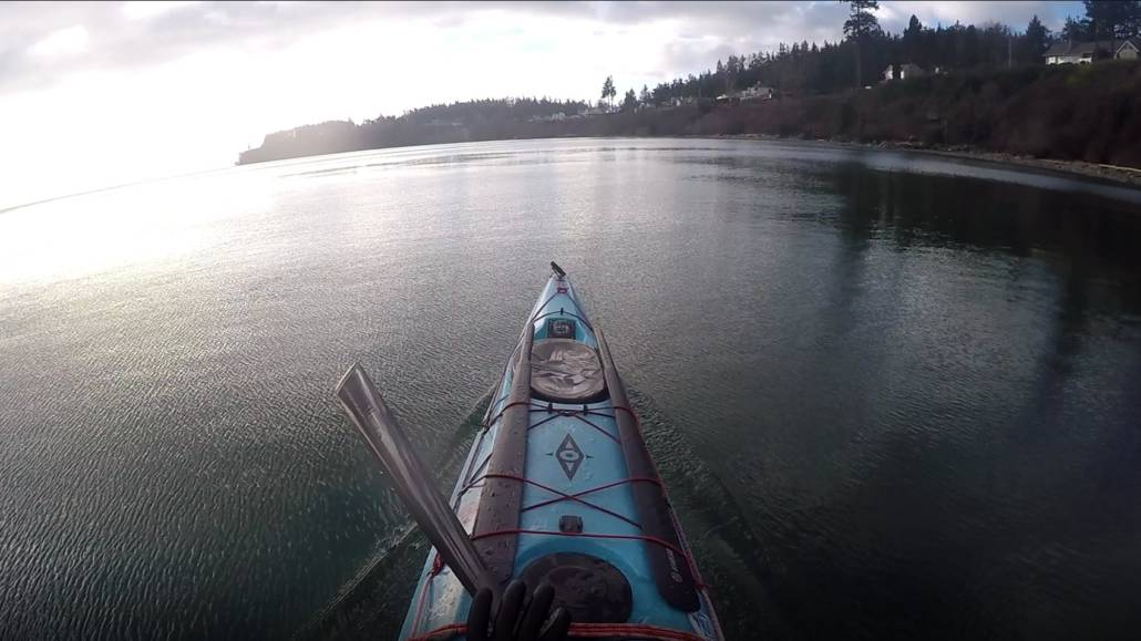 A paddler's view from the cockpit of a sea kayak on flat water