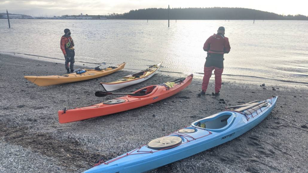 4 kayaks on the beach and calm water