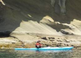 Paddling the Whisky 16 along a cliff face at Sucia Island