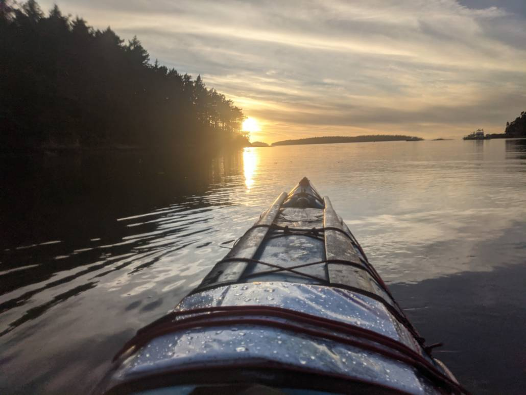 The bow of a sea kayak on the water at sunset