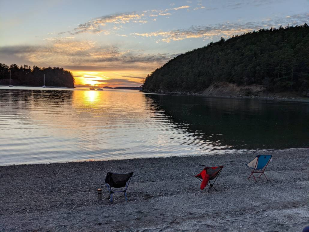 camping chairs on a beach at sunset