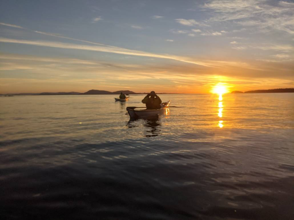 Kayakers on the water at sunset