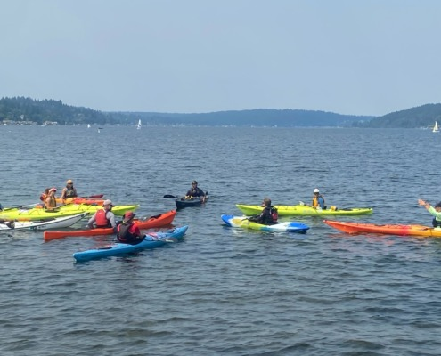 Advanced Communications Workshop photo by Joe Moore of Adaptive Expeditions showing 9 sea kayaks in a star pattern on Lake Washington