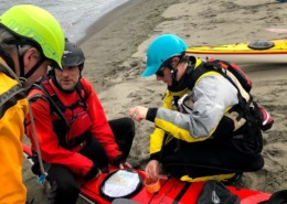 Discussing a hatch cover replacement during a sea kayaking trip