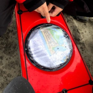 Pointing to a nautical chart inside a kayak hatch