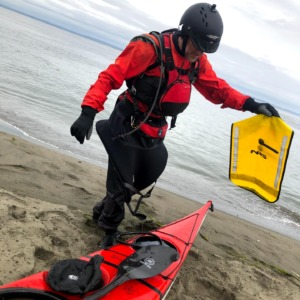 Robert Nissenbaum holding an NRS paddle float with a sea kayak on the beach
